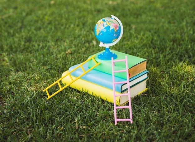 Mini globo em cima da pilha de livros didáticos Foto gratuita
