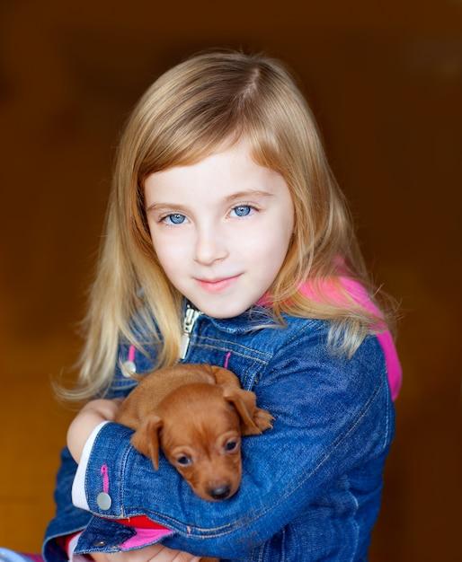 Mini mascote de cachorrinho pinnscher com garota garoto loiro Foto Premium