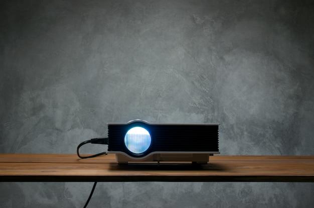 Mini projetor conduzido na tabela de madeira em um conceito do cinema em casa do projetor da sala. Foto Premium