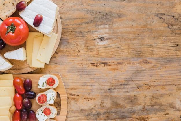 Mini sanduíches com blocos de queijo e tomate na mesa de madeira Foto gratuita
