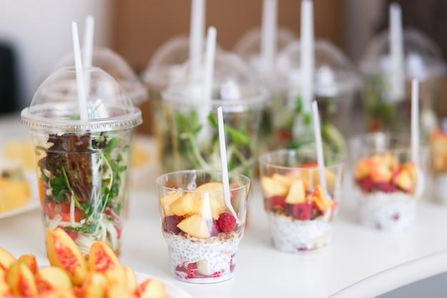 Mini sobremesas e saladas microgreen vegetais saudáveis em copos de plástico canapés. Foto gratuita
