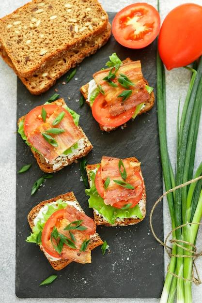Mini torrada de pão integral com tomate, bacon, alface e cebolinha Foto Premium