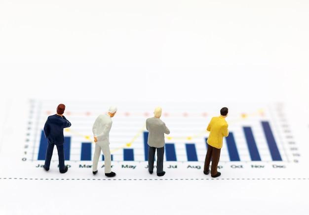 Miniatrue pessoas: empresário, olhando para o gráfico. Foto Premium