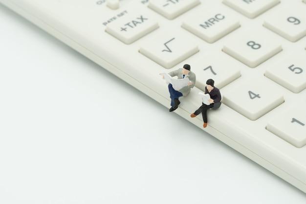 Miniatura 2 pessoas sentadas na calculadora branca Foto Premium