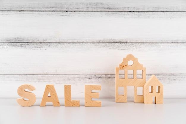 Miniatura de casa e letras de venda de madeira Foto gratuita