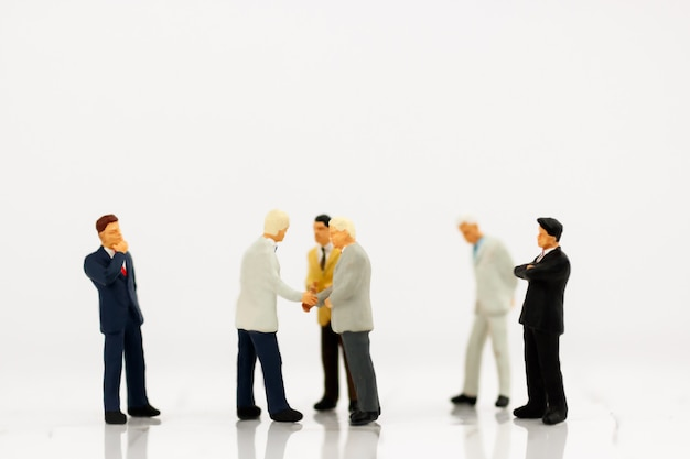 Miniatura de empresários aperto de mão com parceria Foto Premium