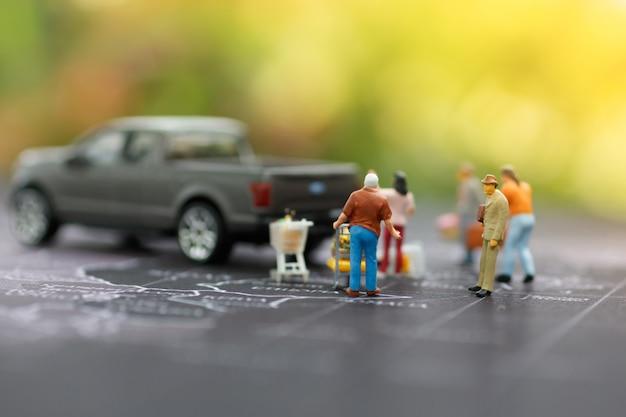 Miniatura de família com carrinho de compras e pegar o carro no mapa Foto Premium