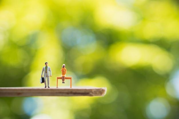 Miniatura de pessoas, homem de negócios e mulher viajando em fundo verde natureza usando para negócios huma Foto Premium