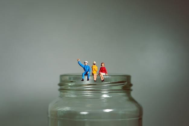 Miniatura de pessoas, homem e mulher sentada na garrafa de vidro Foto Premium
