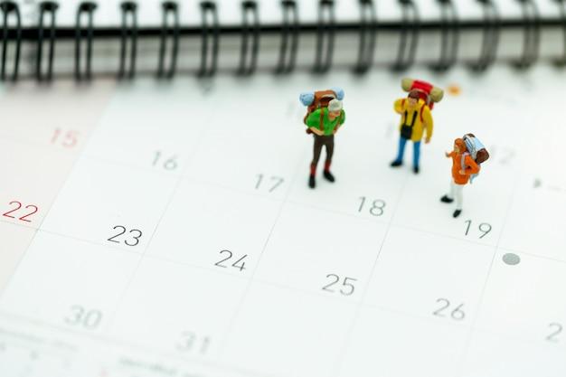 Miniatura de turistas com mochilas de pé no calendário de viagens Foto Premium