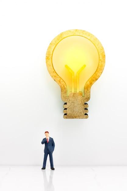 Miniatura do empresário pensando com idéia de lâmpada Foto Premium