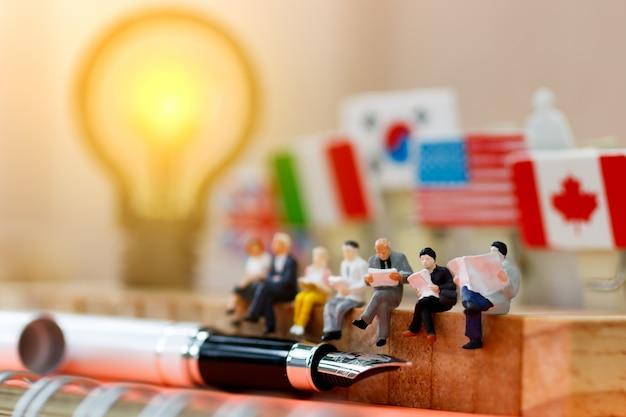 Miniatura pessoas lendo no bloco de madeira Foto Premium