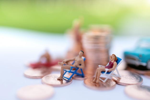 Miniatura pessoas sentadas na praia com moedas Foto Premium