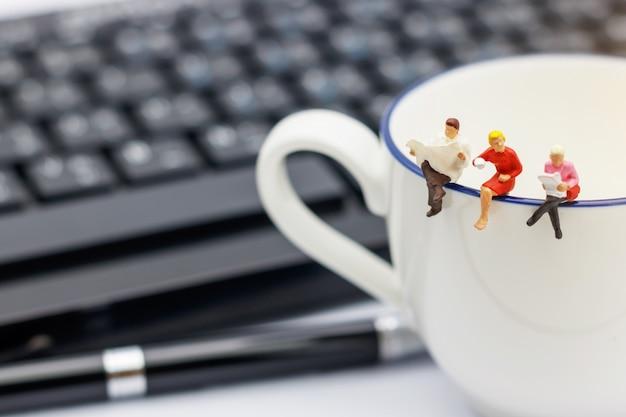 Miniatura pessoas sentadas na xícara de café com teclado e caneta. Foto Premium