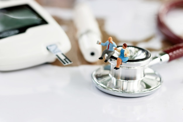 Miniatura pessoas sentadas no estetoscópio e glicose medidor de diabetes. Foto Premium