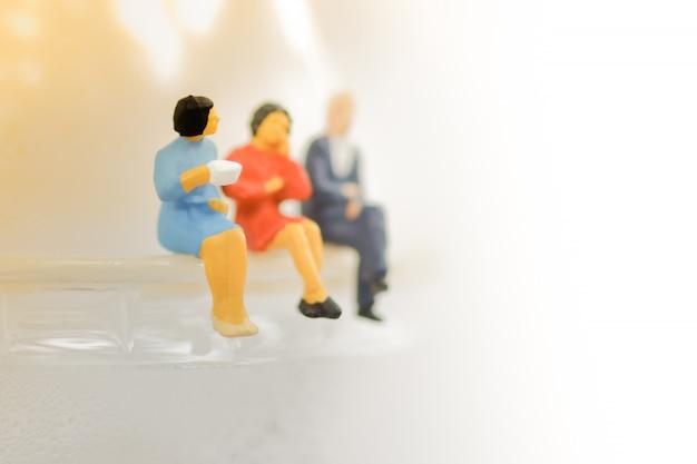 Miniaturas de pessoas sentadas em uma xícara de café com bebida de café Foto Premium