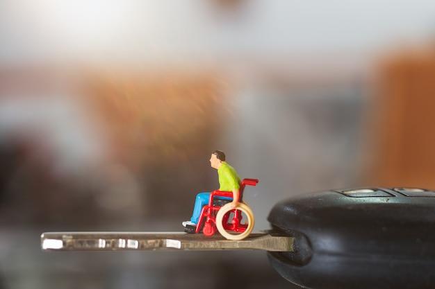 Miniature people disabled man sentado na cadeira de rodas Foto Premium