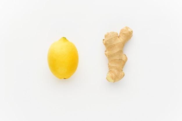 Minimalismo limão e gengibre em um fundo branco. conceito de aumentar a imunidade no inverno Foto Premium