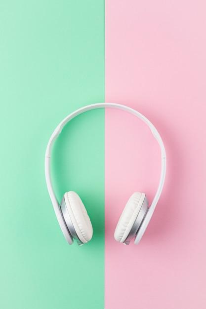Mínimo plano leigos com fones de ouvido sem fio sobre fundo rosa e luz hortelã. Foto Premium