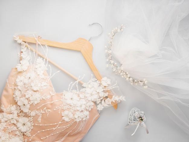 Mínimo plano leigos com vestido de noiva no cabide e véu com miçangas no fundo claro Foto Premium