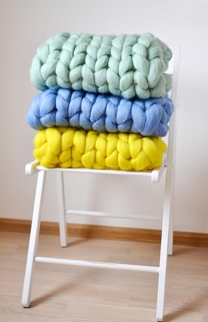 Mint pink pink mint amarelo azul cobertor de lã de merino malha em branco de madeira cadeira de tamborete interior da casa Foto Premium