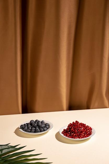 Mirtilos e sementes de romã no prato com folha de palmeira sobre a mesa contra a cortina marrom Foto gratuita