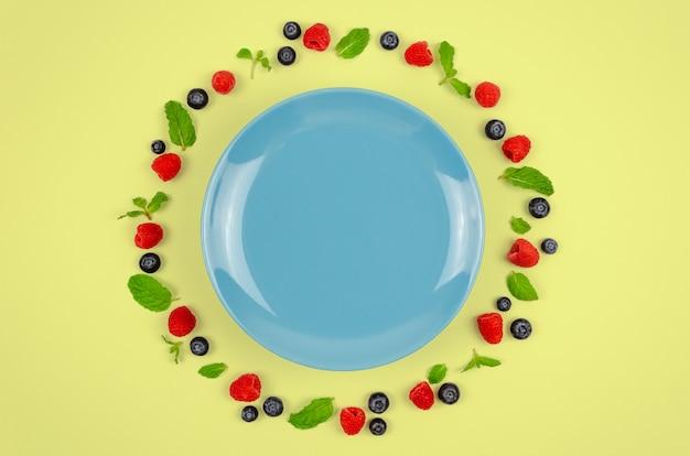 Mirtilos frescos, framboesas e folhas de hortelã com placa azul. Foto Premium