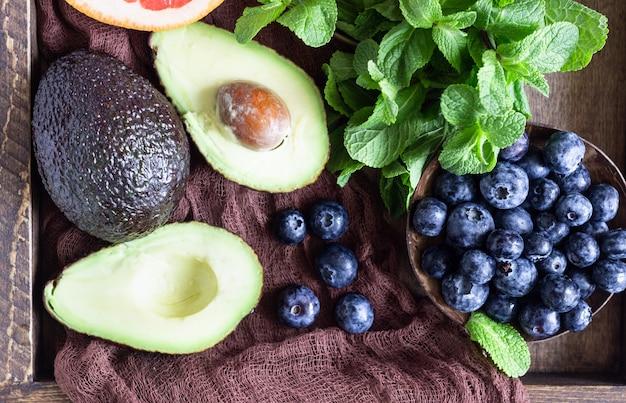 Mirtilos frescos, hortelã, abacate e toranja na bandeja de madeira. comida saudável. seleção clara de comer. café da manhã ou almoço de verão. Foto Premium