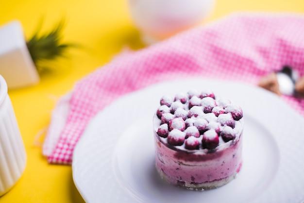 Mirtilos frescos no prato branco contra pano de fundo amarelo Foto gratuita