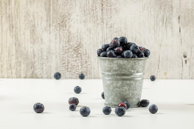 Mirtilos maduros saborosos em um balde pequeno de metal sobre fundo branco e grunge, vista lateral. Foto gratuita