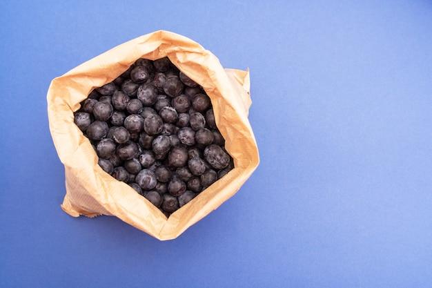 Mirtilos, mirtilos maduros e suculentos no saco de papel sobre o azul, isolado. Foto Premium