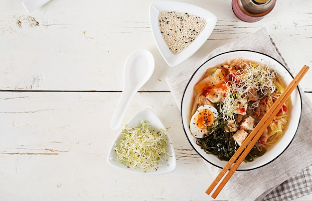 Miso ramen macarrão asiático com couve kimchi, algas, ovos, cogumelos e tofu de queijo em uma tigela na mesa de madeira branca. Foto gratuita