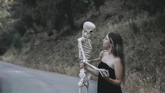 Misteriosa mulher segurando o esqueleto Foto gratuita