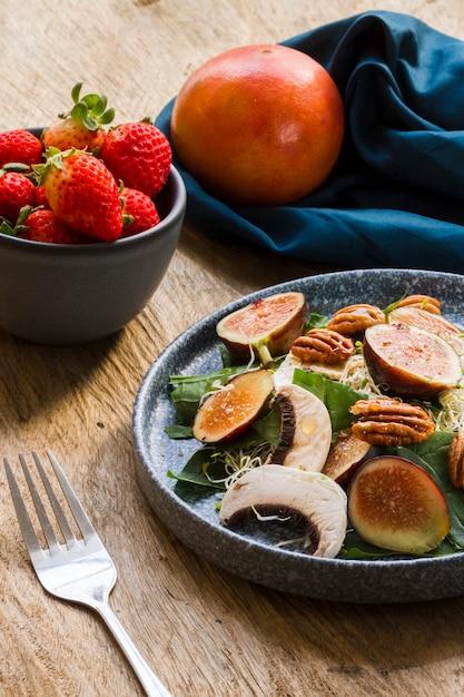 Mistura de alto ângulo de figos e nozes no prato com morangos Foto gratuita