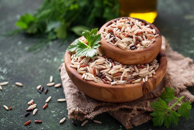 Mistura de arroz marrom, vermelho e selvagem na tigela Foto Premium