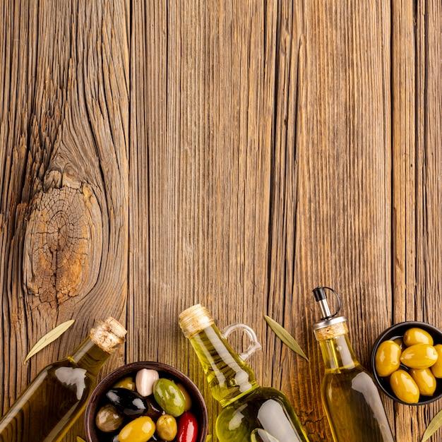 Mistura de azeitonas em tigelas e garrafas de azeite com espaço para texto Foto gratuita