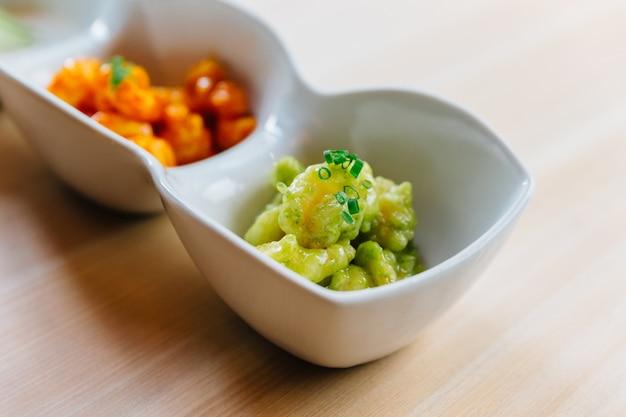 Mistura de camarão de pipoca com molho de mil ilhas e molho de wasabi servido com alface em maionese. Foto Premium