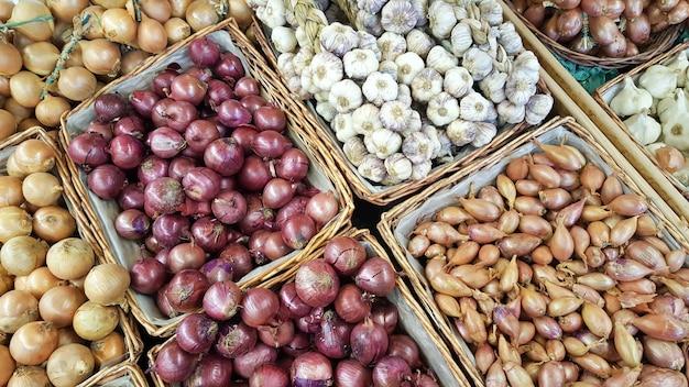 Mistura de cebola bulbo em cestas de venda no balcão do mercado Foto Premium