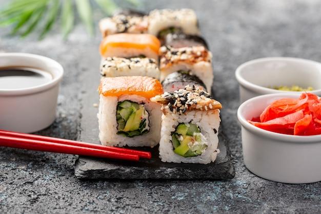Mistura de close-up de rolos de sushi maki com pauzinhos Foto gratuita