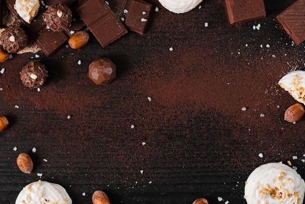 Mistura de doces de chocolate plana leigos no fundo rosa com espaço de cópia Foto Premium