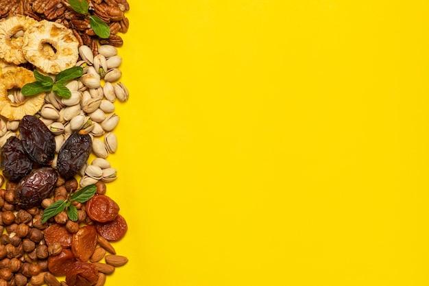 Mistura de frutas secas e secas ao sol e nozes em fundo amarelo com espaço de cópia. símbolos do feriado judaico de tu bishvat Foto Premium