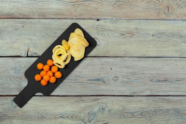Mistura de lanches: biscoitos, biscoitos, salgadinhos e nachos em cima da mesa Foto Premium