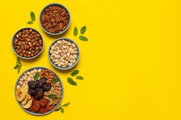 Mistura de nozes e frutas secas em um prato em fundo amarelo com espaço de cópia. símbolos do feriado judaico de tu bishvat lanche saudável - mistura de nozes orgânicas e frutas secas. Foto Premium