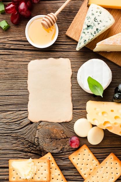 Mistura de queijo plana leigos mel e uvas com cartão em branco Foto gratuita