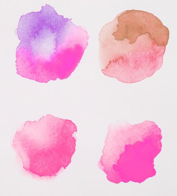 Mistura de tintas rosas, marrons e roxas em papel branco Foto gratuita