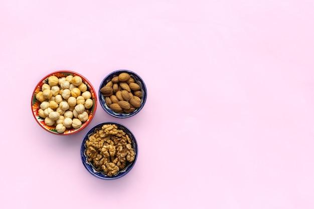 Mistura de variedade de nozes, avelãs, amêndoas, nozes em tigelas. vista plana, vista superior Foto Premium