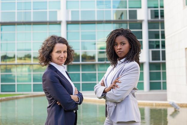 Mistura feminina bem sucedida correu parceiros de negócios posando fora Foto gratuita