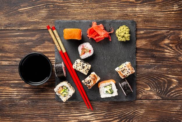 Mistura plana leiga de rolos de sushi maki com pauzinhos Foto gratuita