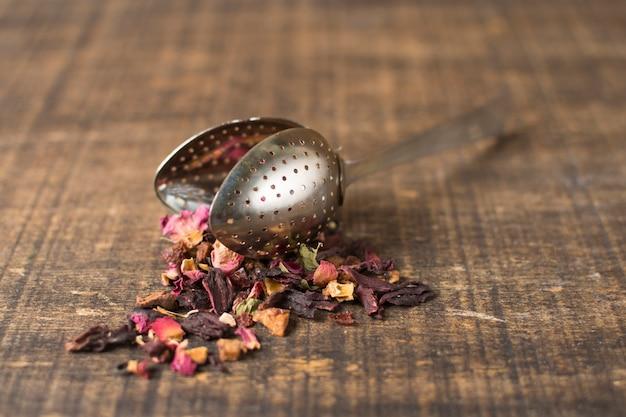 Mistura seca de chá de ervas frutas floral com pétalas derramadas de coador de chá na prancha de madeira Foto gratuita