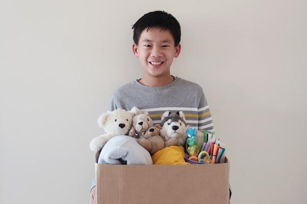 Misturado asiático jovem voluntário pré-adolescente adolescente segurando uma caixa cheia de brinquedos usados Foto Premium